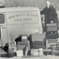 Black and white photograph of projectionist, Bill McDonald, loading all his equipment in a Highlands and Island Film Guild van