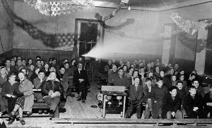 Black and white photograph of an Orkney audience enjoying a cinema screening in a local hall, circa 1950s. Image Credit: Orkney Island Council. Licensor: www.scran.ac.uk