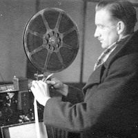 Black and white photograph of George Horne, the first of the Highlands and Islands Film Guild operators, setting up the projector ready for a screening